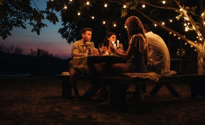 Two couples having a romantic dinner outdoors. We'll have outdoor and indoor seating areas where you can socialise with friends and other campers. Our Glastonbury glamping will have all the social elements for you to enjoy fun with friends and/or family! We welcome everyone!