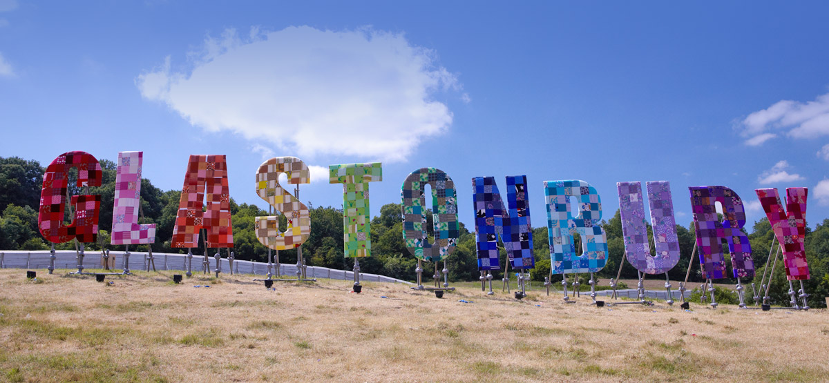 Glastonbury Festival is the most magical place on earth. This rainbow sign is famous worldwide. Come and stay with us for Glastonbury Festival accommodation!