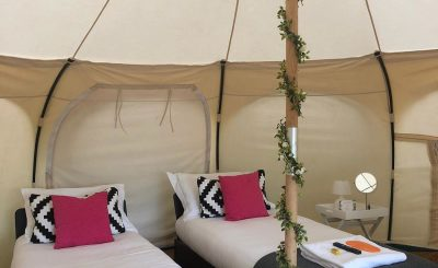 One of our Lotus Belle tents set up with two single real wooden beds. Perfect for two friends! We can also set these up with a double bed for a couple, or more combinations. All our beds are real wooden frames with comfy mattresses, duvets and pillows! The perfect night's sleep at Glastonbury Festival!