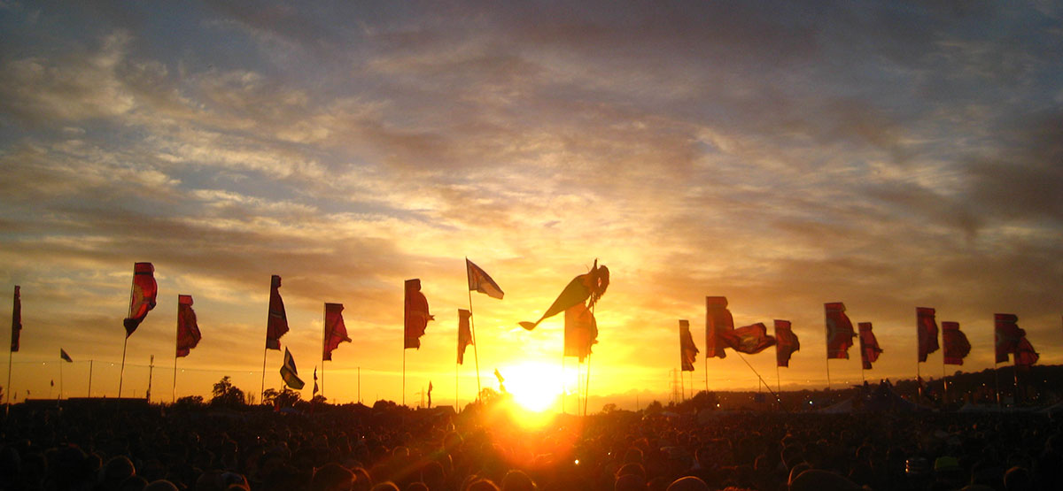 Another magical sunset of the Glastonbury Festival site - the flags flapping in the breeze. We offer the best camping accommodation just minutes from the Pink Gate.