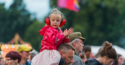 Young girl sat on her parents shoulders in a pink jacket with ear defenders and face paint on. Come and enjoy quality family time at Glastonbury Festival with none of the stress of camping on site. All the amenities you could need including hot showers, flushing toilets, on site restaurant and hot tubs.