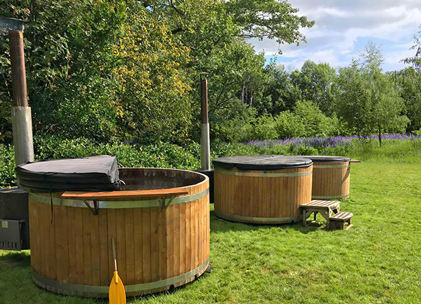 Relax in our Finnish-style wooden hot tubs looking out over the Glastonbury Festival site - luxury camping